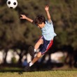 Young boy kicking a soccer ball in the park — Stock Photo