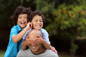Mixed race father and sons playing outside — Stock Photo
