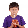 Young boy drinking from orange glass — Stock Photo