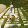 图库照片: Girl in white jumping on computer keyboard monument