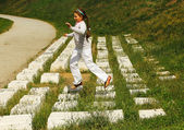 Girl in white jumping on a computer keyboard monument — Stock Photo