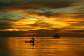 Sailing boat on the sea, a man on a beautiful golden sunset — Stock Photo