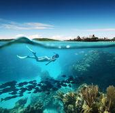 Jonge vrouw snorkelen in het koraalrif in de tropische zee tegen de achtergrond van de eilanden — Stockfoto