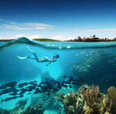 Young woman snorkeling in the coral reef in the tropical sea against the backdrop of the islands — Stok fotoğraf