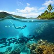 Beautiful Coral reef with lots of fish and a woman — Stock Photo