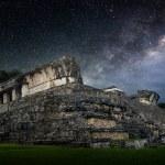 Постер, плакат: Galactic night starry sky over the ancient Mayan city of Palenqu