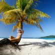 Dreaming womsitting on beach under palm tree on beaut — Stock Photo #22015453