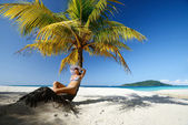 Dreaming woman sitting on the beach under a palm tree on a beaut — Stock Photo