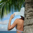 Woman under a palm tree watching the ocean dream — Stock Photo #24039551