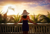 A woman on a balcony looking at the beautiful Caribbean sunset — Stock Photo