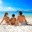 Happy family sunning on the beach on the background of the islan — Stock Photo