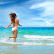 Young beautiful girl running on the beach — Stock Photo
