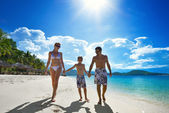 Happy family walks along the white sandy beach — Stock Photo