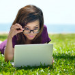 Picture of smiling Asian student working on a laptop outdoors — Stock Photo