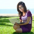 Pretty Asian girl sitting with a laptop in the park on the grass — Stock Photo #28475405