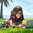 Pretty Asian girl is resting under the palm trees on the grass w — Stock Photo