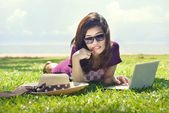 Pretty young asian woman is dreaming with a laptop lying on the — Stock Photo