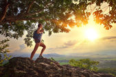 Young woman admires the sunset with a backpack standing on cliff — Stock Photo