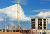 Construction of concrete buildings on background moving clouds i — Stock Photo