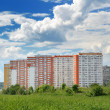 Stock Photo: Modern 17-storey yellow-orange house in green arenear Mo