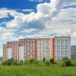 The modern 17-storey yellow-orange house in a green area near Mo — Stock Photo