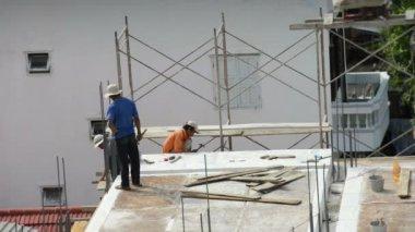Trzy azji pracowników pracujących przy budowie nowego budynku wieżowiec. — Wideo stockowe