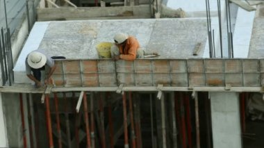 Vietnamese builders install metal walls for pouring concrete in the frame of the building — Stock Video