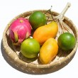 Foto Stock: Fresh tropical fruit on wicker plate on white background