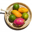 Photo: Fresh tropical fruit on wicker plate on white background.