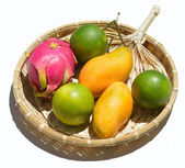 Fresh tropical fruit on a wicker plate on a white background — Stockfoto