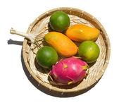 Fresh tropical fruit on a wicker plate on a white background. — Stockfoto