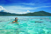 Happy girl with a mask floating in the azure tropical sea — Stock Photo