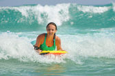Young attractive woman bodyboards on surfboard with nice smile — Stock Photo
