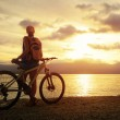 Young woman with backpack standing on the shore near her bicycle — Stock Photo #38847597