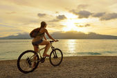 Young woman with backpack standing on the shore near his bike an — Stock Photo