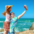 Happy couple taking a photo on a beach on holidays — Stock Photo