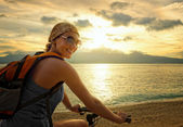 Young woman with backpack standing on the shore near his bike an — Foto de Stock