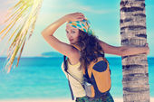 Happy young woman standing with backpack on coast sea and lookin — Stock Photo