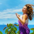 Happy young woman jumping over blue sky. — Stock Photo