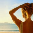 A back side view on a wonderful young woman watching to sea and — Stock Photo #50535141