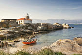 Red boat and lighthouse — Stock Photo