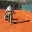 Rolling a tennis court - Stock Photo