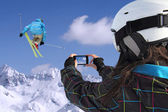Mobile phone photographs of skiers jump — Stock Photo