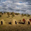 Stock Photo: Clay bild round huts and wooden fence, Africa