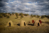 Clay bild round huts and wooden fence, Africa — Stock Photo