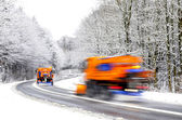 Snow plows on winter road, vehicles blurred — Stock Photo