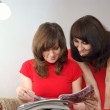 Foto Stock: Young two women in reading magazine. Reading at home