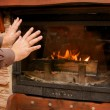 Man warms up by the fire / fireplace - Stock Photo