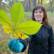 Woman holding chestnut leaf — Stock Photo