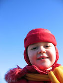 Little girl laughing in a red hat with ear flaps on blue sky background — Stock Photo
